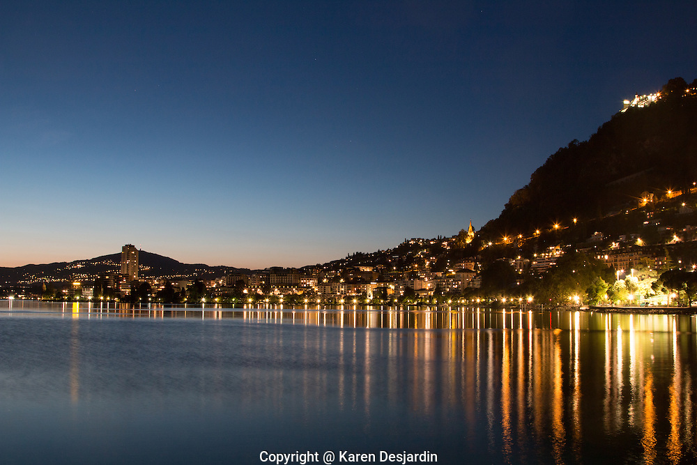 The lights of Montreux, Switzerland are reflected in the waters of Lake Geneva at dusk.
