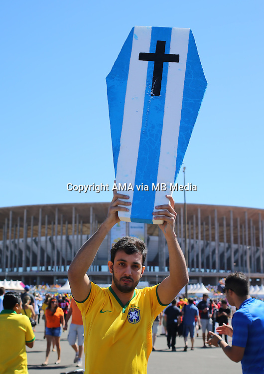 A fan of Brazil holds up a coffin painted in the colours of Argentina as he makes his way to  The National Stadium / Estadio Nacional Mane Garrincha in Brasilia, Brazil, host venue of the FIFA 2014 World Cup