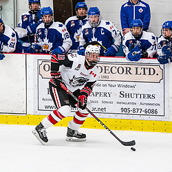 GEORGETOWN, ON - MARCH 2: Mitchell Hewitson #18 of the Georgetown Raiders carries the puck past the Markham Royals bench March 2, 2019 at Gordon Alcott Memorial Arena in Georgetown, Ontario, Canada.<br /> (Photo by Dave Fryer / OJHL Images)