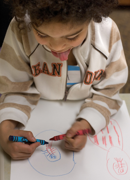 "Miguel Santiago-Flores concentrates as he draws aliens during the ""It Takes a Village"" program at O.U.'s Multicultural Center on Monday, 1/15/07. The program's goal was to teach tolerance through interactive activities for children."