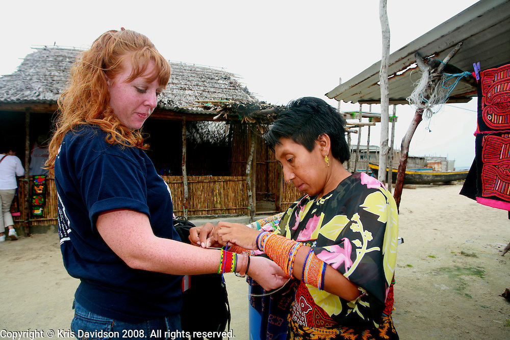 A Kuna woman ties traditional Kuna bracelets on a traveler. Each Kuna bracelet is said to tell a story. ..Image made on San Blas in the Kuna Yala region of Panama. Kuna Yala includes a band of rainforest that extends for 125 miles along the Caribbean coast nearly to the border of Colombia and encompasses some 365 tiny isles with white-sand beaches lapped by crystalline waters. For travelers interested in tropical nature, the seaside, and indigenous cultures, Kuna Yala is an ideal destination. ..The Kunas are proud and independent, protecting themselves from the influence of massive tourism since a revolution in 1925 in which they obtained semi-political autonomy in Panama.  .
