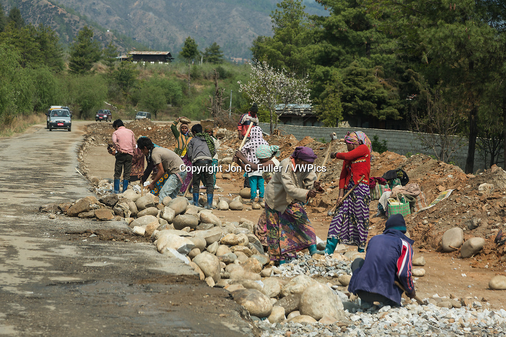 A crew of Nepalese or Indian women work with sledgehammers, breaking rocks on a road repair construction job in Bhutan.