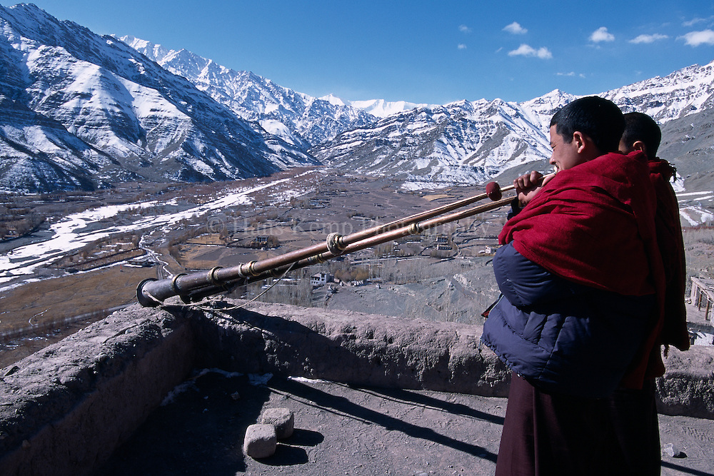 Monks on the roof of Matho monastery announcing the start of a festival.Matho, Ladakh, India.