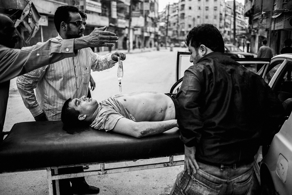 Aleppo, Syria, 2012/10/09.<br /> In front of Dar Al-Shifaa hospital.<br /> A wounded man, treated by physicians is going back home in a private car, due to the lack of ambulances.