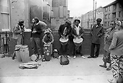 A group of street musicians gathered in front of a brick wall playing congas and jembes to passers by, Notting Hill Carnival, London, 1989