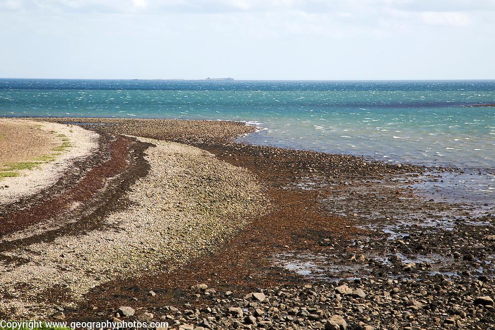 Stoney beach at low tide, Holy Island, Lindisfarne, Northumberland, England, UK