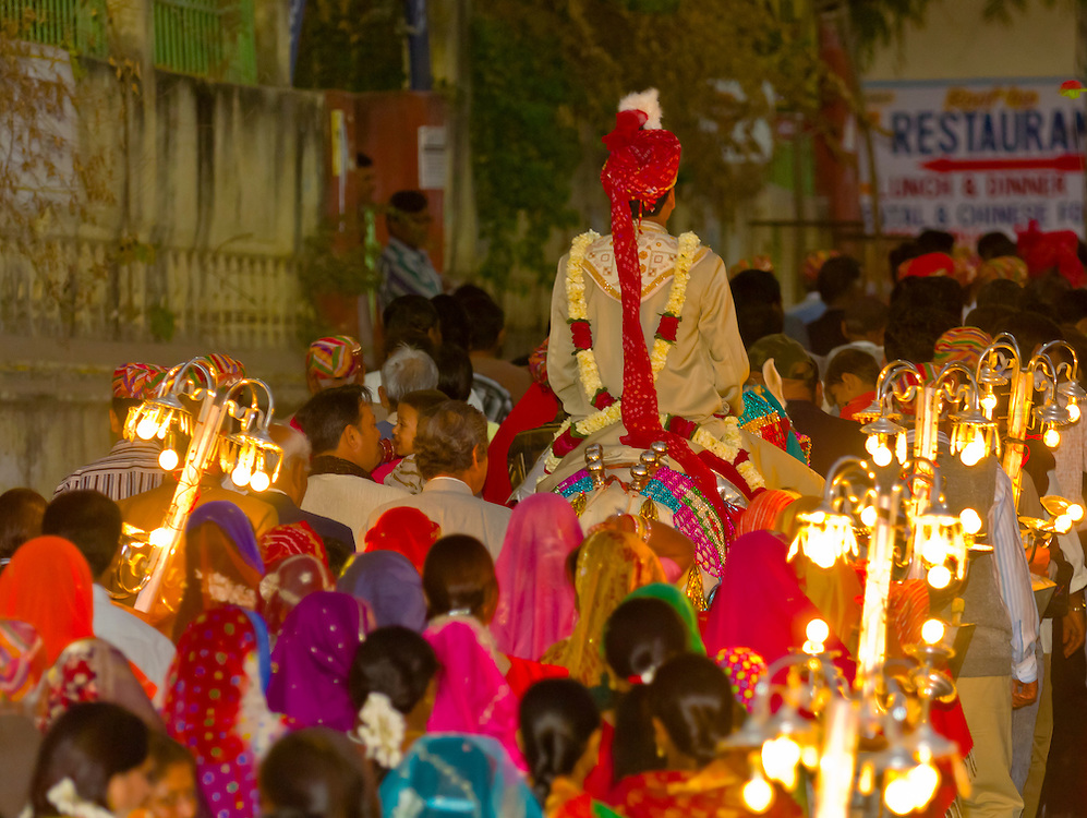 Wedding procession following the bride groom on horseback through the streets of Udaipur, Rajasthan, India