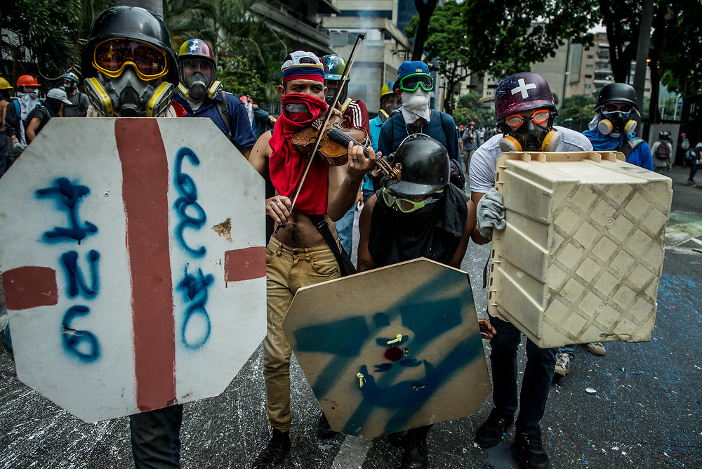 """CARACAS, VENEZUELA - MAY 8, 2017: Wuilly Arteaga, 23, plays the National Anthem on his violin, flanked by members of """"The Resistance"""" who use homemade shields to protect Mr. Arteaga from the hundreds of rubber bullets, buckshot and tear gas canisters that rain down on protesters each day.  Mr. Arteaga has become an icon the months of street protests that have shaken Venezuela. He regularly braves rubber bullets, buckshot, being tear gassed, and hit by police water cannons to play the National Anthem on the front lines of clashes between anti-government protesters and security forces. Videos of Mr. Arteaga in tears went viral in Venezuela when authorities broke his violin, causing him to become a National internet sensation.  Recently Mr. Arteaga was flown to the United States where Latin musicians Marc Anthony and Oscarcito met with him and presented him with a new violin.  PHOTO: Meridith Kohut"""