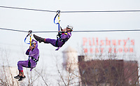 Minneapolis, MN - January 26, 2017: Bold North Zip Line riders, wearing a purple unicorn costumes, zoom down the line and over the Mississippi River as part of the SuperBowl LII events taking place in Minneapolis.