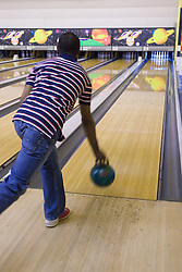 Young man bowling a ball down an indoor ten pin bowling alley,