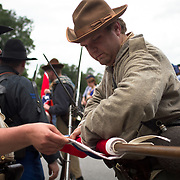 Dan Wambaugh, of Charlotte, Michigan, rolls the Confederate flag as part of the Color Guard that lead Garnett's Brigade in the Pickett's Charge Commemorative March during the Sesquicentennial Anniversary of the Battle of Gettysburg, Pennsylvania on Wednesday, July 3, 2013.  The Battle of Gettysburg lasted from July 1-3, 1863 resulting in over 50,000 soldiers killed, wounded or missing.  John Boal Photography