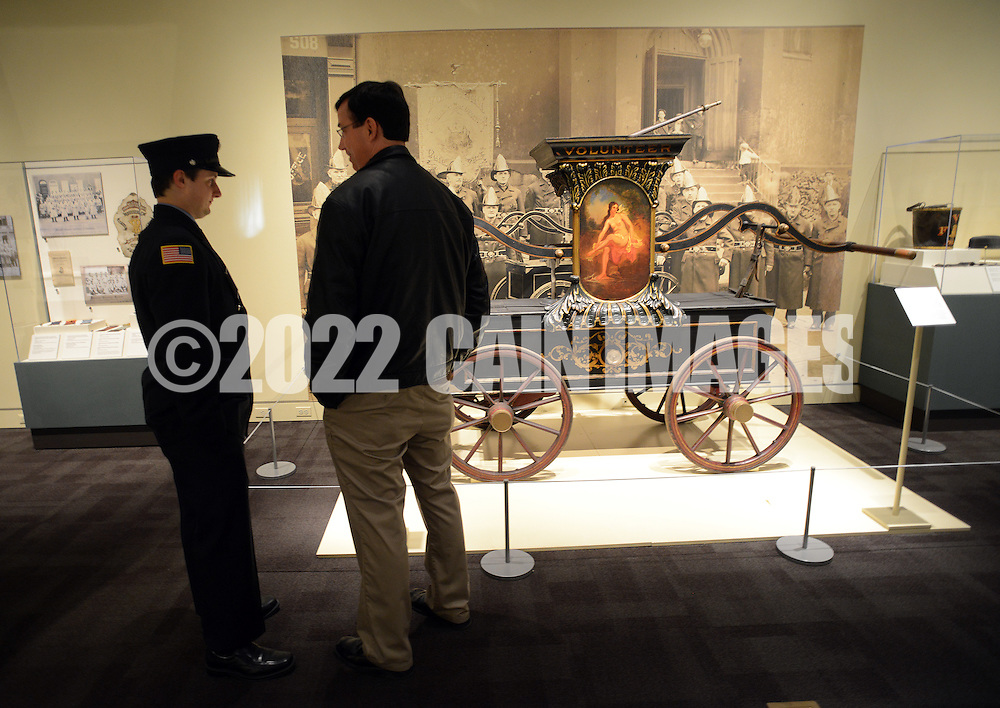 """Sam Tilley (L), 19, and his uncle Mike Tilley, both of Doylestown, Pennsylvania look at a fire engine from the early 1900's during a special preview of the Mercer Museum's new exhibit """"To Save Our Fellow Citizens:"""" Volunteer Firefighting, 1800-1875 Thursday April 23, 2015 in Doylestown, Pennsylvania. The exhibit tells the exciting story Philadelphia's volunteer firefighters and fire companies as the city grew and expanded during the 1800's.  (Photo by William Thomas Cain/Cain Images)"""