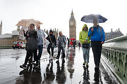 © Licensed to London News Pictures. 20/08/2016. LONDON, UK.  Tourists are caught in a heavy rain shower near Big Ben in Westminster in London today. Following the UK's mini heatwave this week, weather forecasters have issued a severe weather warning, predicting a spell of wet and stormy weather across the country.  Photo credit: Vickie Flores/LNP