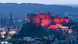 Evening view of Edinburgh Castle illuminated in red from Salisbury Crags, Edinburgh, Scotland, United Kingdom.