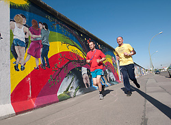 Men jogging beside Berlin Wall at East Side Gallery with murals painted on wall in Berlin Germany