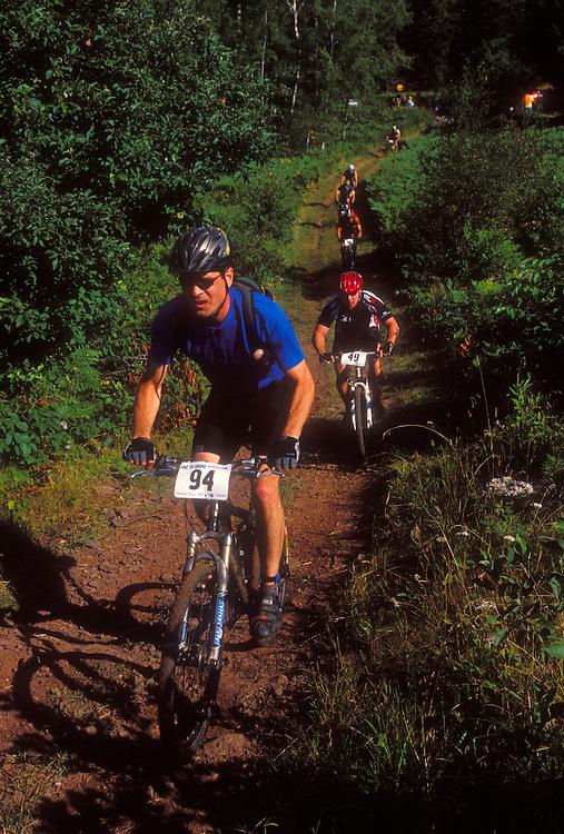 Mountain bikers in the Ore to Shore race climb a hill near Ishpeming, Mich.