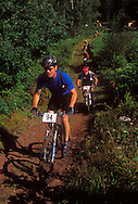 Mountain bikers in the Ore to Shore race climb a hill near Ishpeming, Mich.