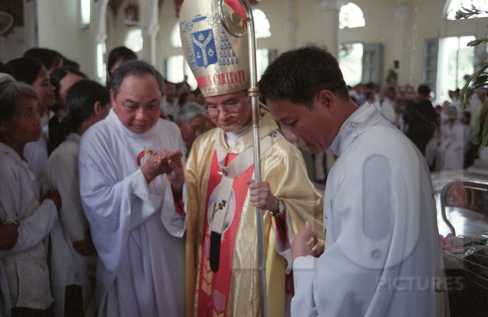 Two vietnamese priest are helping an old bishop to walk through the church. Nam Dinh province, Vietnam, Asia