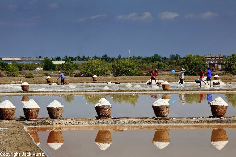Mar 23, 2009 -- SAMUT SONGKHRAM, THAILAND: Workers harvest salt near Samut Songkhram, Thailand. The salt farms between Samut Sakhon and Sumat Songkhram are Thailand's largest salt producing region. Salt is typically harvested for about six months of the year. The fields are prepared for salt farming as soon as the rainy season ends. First the fields are tamped down so they hold water, then they are flooded with salt water from either the Gulf of Siam or the Mae Khlong River (both are salty). After about two months, the first harvest is ready. The fields are drained and the salt picked up from the fields. Then the fields are flooded again and the process repeated. As the season goes on and the fields become saltier, the amount of time they are flooded is reduced till the end of the season when they may only be flooded for two or three days. Most of the workers in the salt fields are migrant workers from Isaan, an impoverished region in the northeast of Thailand. Once the rainy season starts and it's no longer possible to harvest salt the workers go home to work their small farms. The workers are paid based on the amount of salt their crew harvests.    Photo by Jack Kurtz