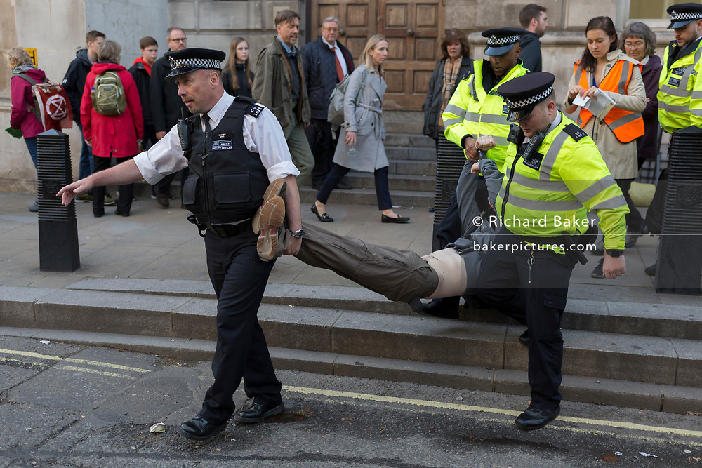 An environmental activist is arrested while protesting about Climate Change during the blockade of Whitehall in central London, part of a two-week prolonged worldwide protest by members of Extinction Rebellion, on 16th October 2019, in Westminster, London, England.