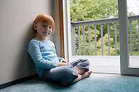 Portrait of young girl (5-6) sitting cross-legged on carpet