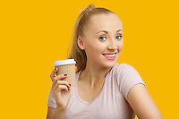 Portrait of beautiful young woman holding disposable cup over yellow background