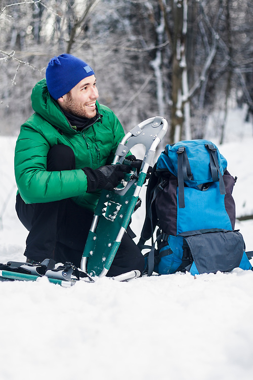 Male Hiker getting ready for a snowshoeing day trip.