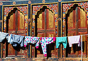 Traditional windows and shutters with modern contemporary clothes drying on a washing line, Bhutan. RESERVED USE - NOT FOR DOWNLOAD -  FOR USE CONTACT TIM GRAHAM