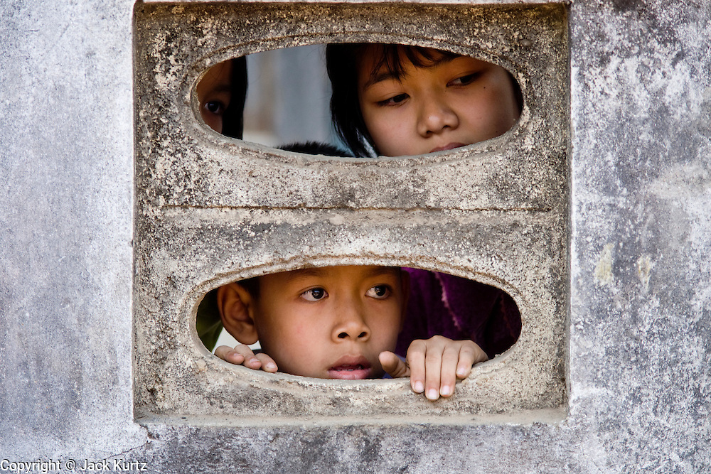 26 FEBRUARY 2008 -- MYAWADDY, MYANMAR: Children a hole in the cement wall around their home Myawaddy, Myanmar (Burma). Myawaddy is just across the Moei River from Mae Sot, Thailand and is one of Myanmar's leading land ports for goods going to and coming from Thailand. Most of the businesses in the town are geared towards trade, both legal and illegal, with Thailand. Human rights activists from Myanmar maintain that the Burmese government controls the drug smuggling trade between the two countries and that most illegal drugs made in Myanmar are shipped into Thailand from Myawaddy.   Photo by Jack Kurtz