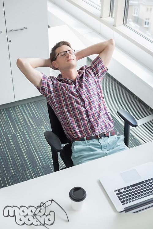 High angle view of businessman relaxing at desk in creative office