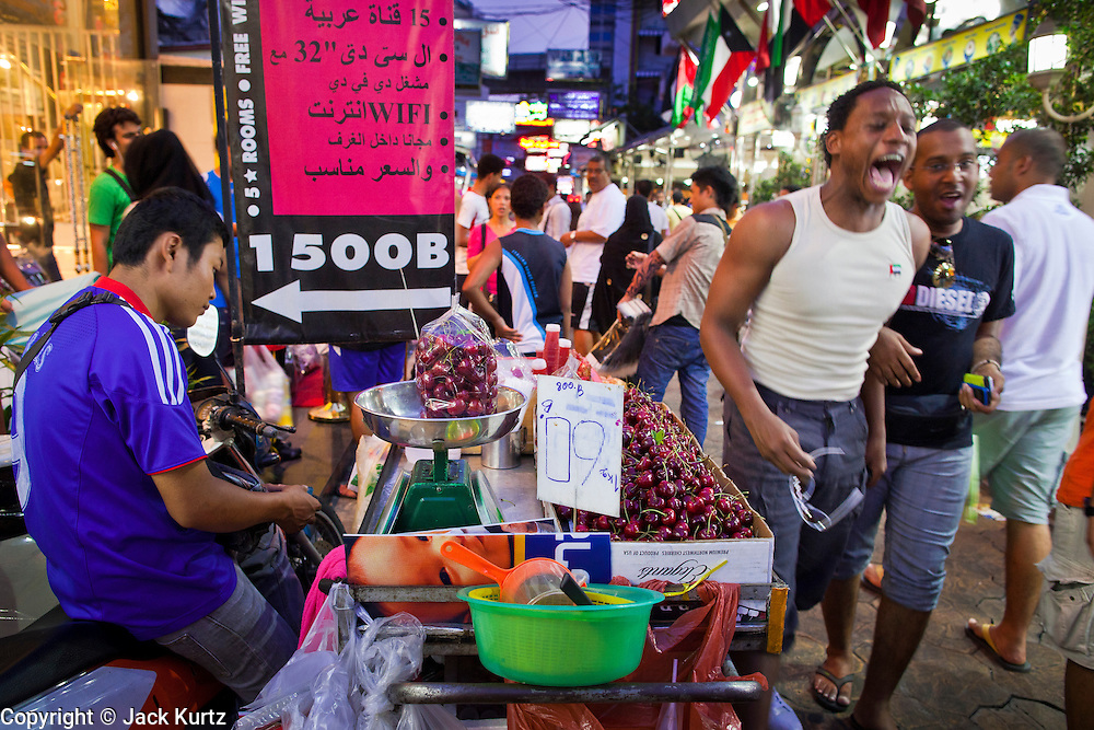 07 JULY 2011 - BANGKOK, THAILAND:   Men from North Africa laugh as they walk by a Thai fruit vendor in the night market in the Soi Arab neighborhood of Bangkok. Soi Arab started as an alleyway in Bangkok (Soi is the Thai word for alley or small street). What started as an alley has now grown into a neighborhood that encompasses several blocks of restaurants, hotels and money exchanges that cater to Middle Eastern visitors to Thailand. The official name of the street is Sukhumvit Soi 3/1, located in North Nana between Sukhumvit Soi 3 and Sukhumvit Soi 5, not far from the Nana Plaza night-life area and the Grace Hotel popular among Arabs.    PHOTO BY JACK KURTZ