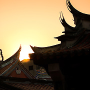 Swallow tail rooves silhouetted by setting sun at Tainan's God of War Temple, Taiwan