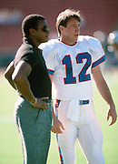 (L-R) Former NFL player and current day sportscaster Ahmad Rashad  talks to Buffalo Bills quarterback Jim Kelly (12) before the NFL preseason football game against the Los Angeles Raiders on Aug. 22, 1987 in Los Angeles. The Bills won the game 7-3. (©Paul Anthony Spinelli)