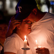 Mary Sarmiento hugs her cousin, Carlos Sarmiento, while she grieves for her son, Parish Ocampo, and her husband, Ulises Ocampo, during the candle light memorial vigil held at Civic Space Park in Phoenix, Arizona. Parish and his dad were shot to death at their home by masked men.