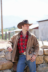 handsome cowboy leaning on a stone wall