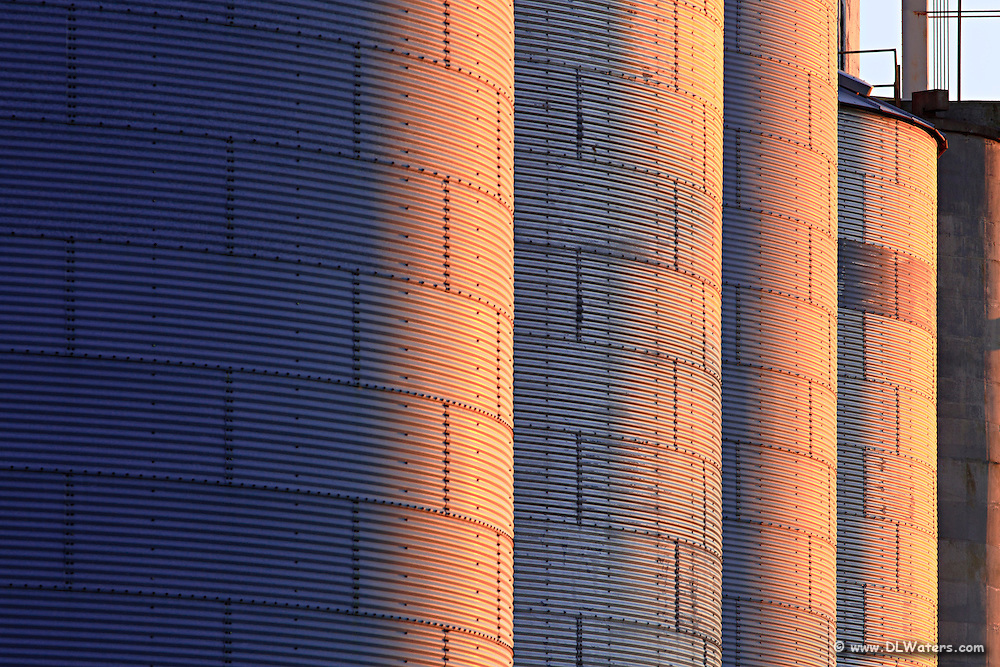 A repeating pattern of silos at sunset.