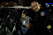 Sacramento Police Department robbery detective Darryl Bryan gets information from a man arrested for possession of methamphetamine while working as a patrol officer on the graveyard shift on  October 26, 2012 in Sacramento, Calif. Budget cuts have decimated the Sacramento Police Department resulting in the elimination of many investigative units.