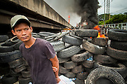 16 MAY 2010 - BANGKOK, THAILAND: Anti government protesters reinforce a burning tire barricade on Rama IV Road Sunday. Thai troops and anti government protesters clashed on Rama IV Road again Sunday afternoon in a series of running battles. Troops fired into the air and unidentified snipers shot at pedestrians on the sidewalks. At one point Sunday the government said it was going to impose a curfew only to rescind the announcement hours later. The situation in Bangkok continues to deteriorate as protests spread beyond the area of the Red Shirts stage at Ratchaprasong Intersection. Many protests now involve people who have not been active in the Red Shirt protests and live in the vicinity of Khlong Toei slum and Rama IV Road. Red Shirt leaders have called for a cease fire, but the government indicated that it is going to go ahead with operations to isolate the Red Shirt camp and clear the streets.      PHOTO BY JACK KURTZ