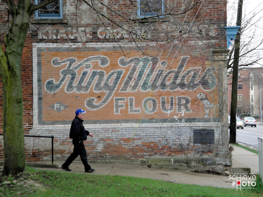 A man walks in front of the King Midas Flour sign on an old grocery store on Williamson Street in Madison, Wisconsin.