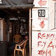 The attendant of a pay-per-use shower facility in Agbogbloshie, a slum in Ghna's capital Accra, dozes in the doorway. A demolition notice, obviously ignored, is painted on the wall.