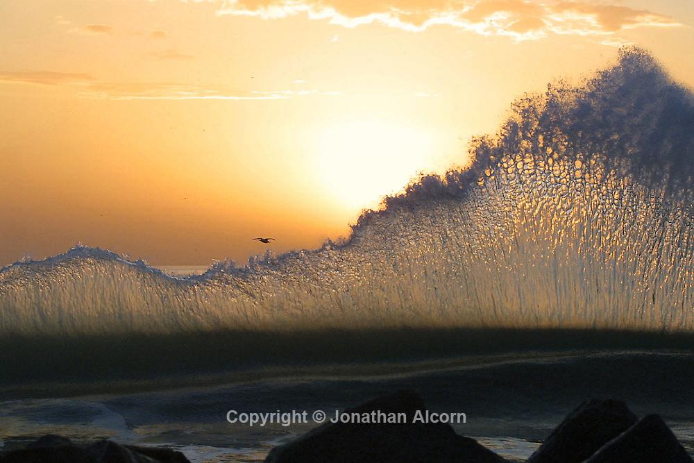 Waves thrash at the  Venice Beach Breakwater at sunset