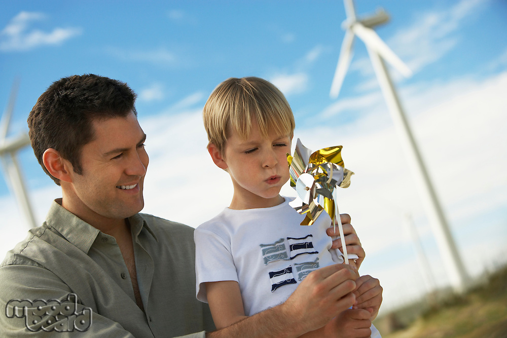 Boy (7-9) blowing toy windmill with father at wind farm
