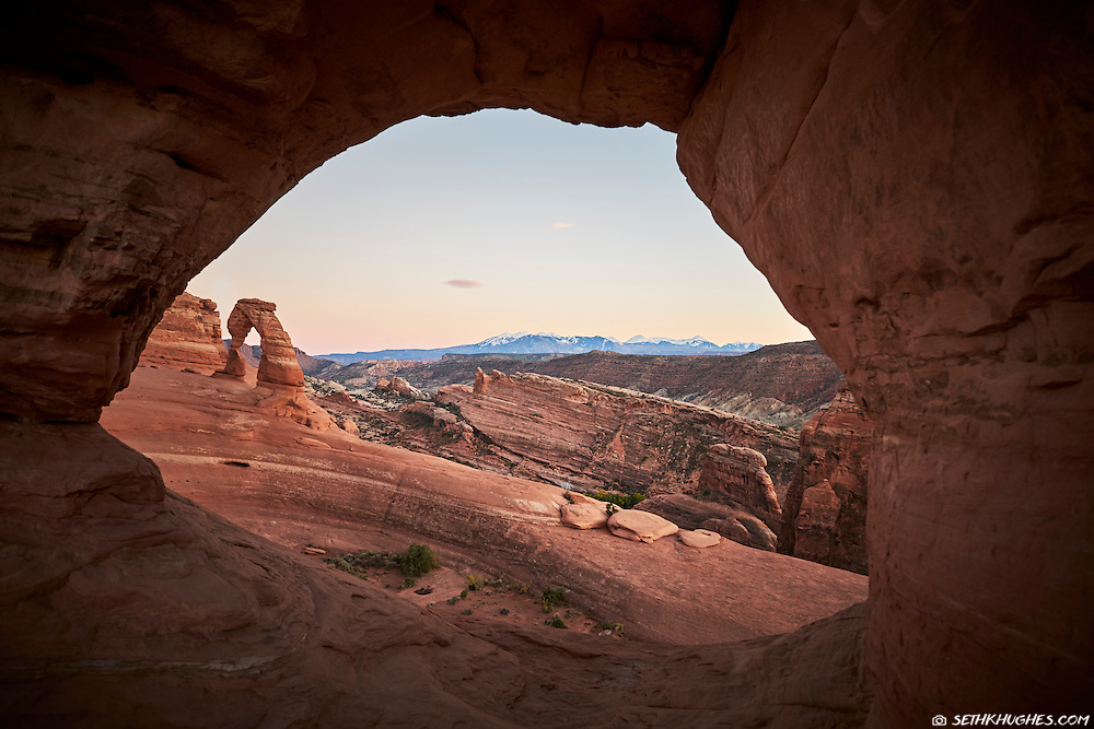 The view through a sandstone window frames the famous Delicate Arch and La Sal Mountains near Moab in Arches National Park, Utah.