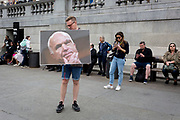 On US President Donald Trump's second day of a controversial three-day state visit to the UK, a man stands with a picture of the late-Senator and Trump opponent, John McCain as protesters voice their opposition to the 45th American President, in Trafalgar Square, on 4th June 2019, in London England.