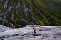 A lone woman treks up to the crater of Mount Bromo, East Java, Indonesia, Southeast Asia