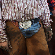 Young Wyatt Flattery wears his father's belt buckle during a cattle roundup at the Bar B ranch near Albia, Iowa.  During rainy and muddy conditions, about a dozen hired hands roped and seperated calves from the herd for vaccinations, branding and the placement of growth stimulant implants.  The male calves were also castrated.  Owner Catherine Bay runs the operation with a herd of over 2,000 cattle.