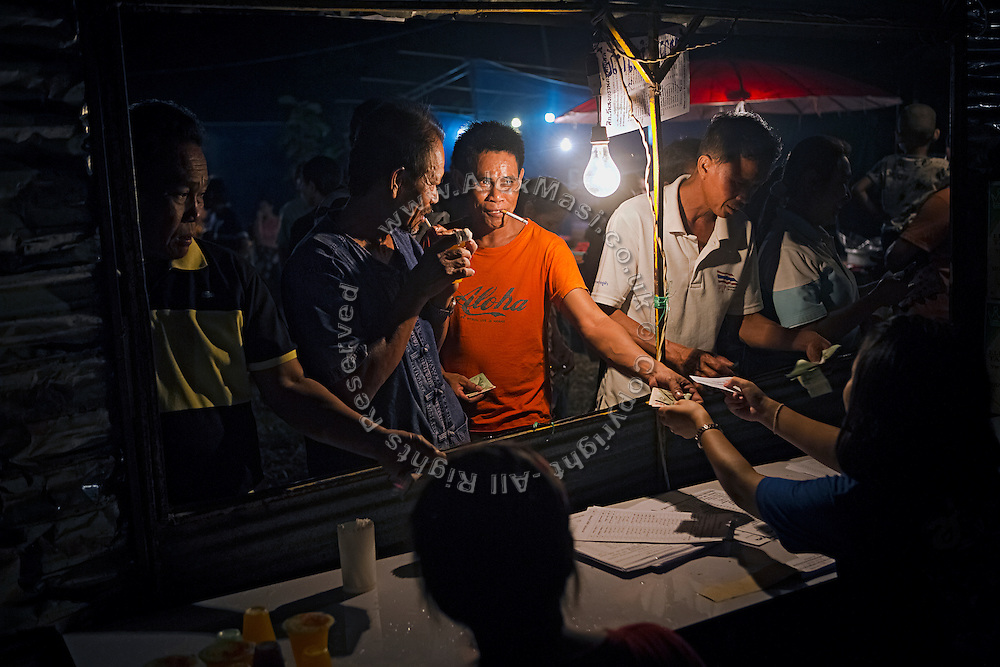 Man are buying tickets before the start of a Muay Thai boxing event, organised in a village near Ubon Ratchathani, northeast Thailand.