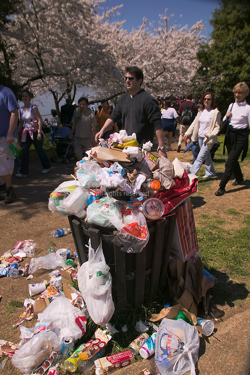 Garbage can surrounded by and overflowing with trash during the Annual Cherry Blossom Festival in Washington DC, USA<br />