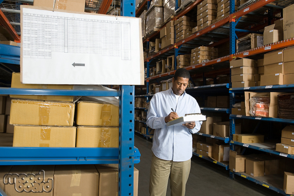 Man inspecting boxes in distribution warehouse