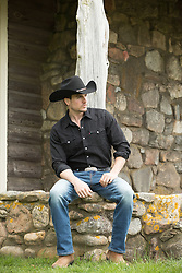 hot cowboy sitting on a stone porch